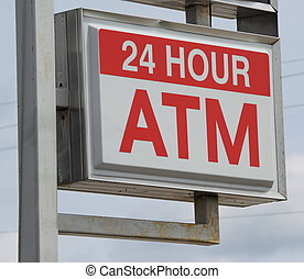 A 24 hour ATM automated teller sign on a post.