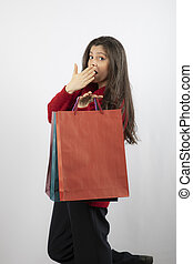 A beautiful young woman with colored shopping bags over white background