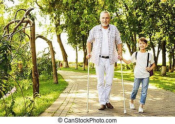 A boy and an old man on stilts for adults are walking in the park. The boy is holding the old man's hand. They happy