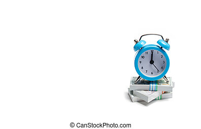 A clock is standing on a bunch of packs of money on a white background. The concept of expressing time is money. Planning time and increase efficiency, increase profits. Side job in free time.