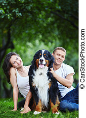 A couple with a dog in park