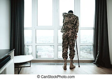 A disabled soldier stands with his hand on the window. He feels sad and depressed. It stands near a large panoramic window, from which you can see the city.