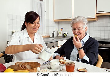 a geriatric nurse helps elderly woman at breakfast. elder care of seniors