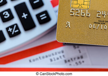 a gold credit card, bank statement and calculator. symbolic photo for cashless transactions and status symbols.