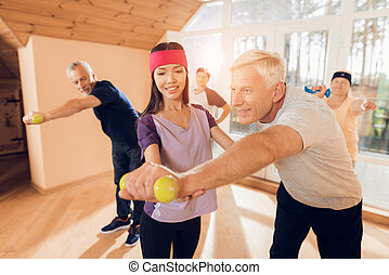 A group of elderly women and men doing therapeutic gymnastics in a nursing home.