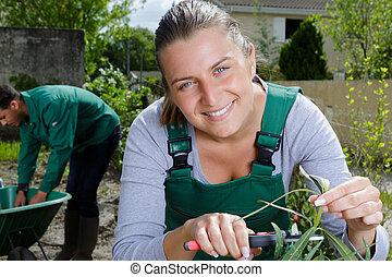 a happy woman cutting a plant