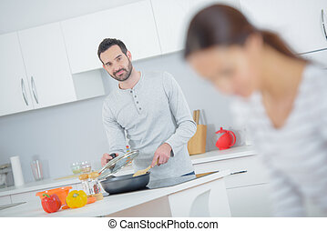 a husband is cooking dinner