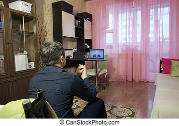 A man is watching a video conference on a laptop. Located in an apartment in self-isolation.