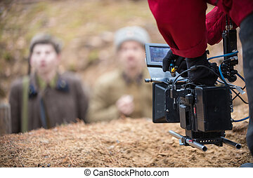 A man with camera in hand is filming the actors