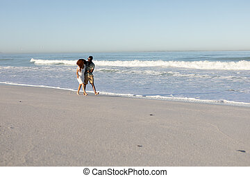 A mixed race couple walking and laughing on beach on a sunny day