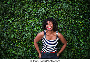 A portrait of a black woman standing against green background of bush leaves.