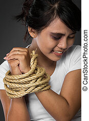 woman with hands tied up with rope being abused