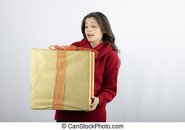 A pretty young woman holding gift box over white background
