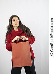 A pretty young woman on white background holding shopping bags