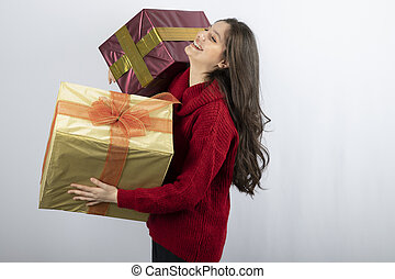 A smiling woman in red sweater holding Christmas presents