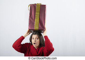 A surprised woman holding a Christmas gift box overhead
