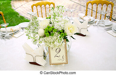 A view of a round banquet table with napkins and silverware set and a colorful flower centerpiece.