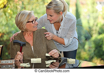 a young blonde woman touching shoulders of an old blonde woman taking a crutch in her hand