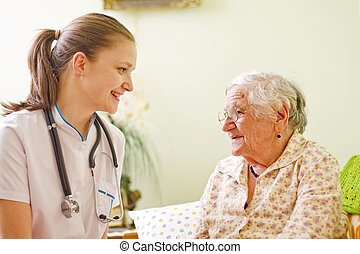 A young doctor / nurse visiting an elderly sick woman socialising - talking - with her.