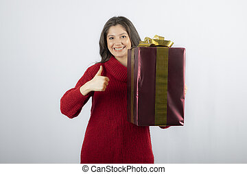 A young woman holding gift box and showing a thumb up
