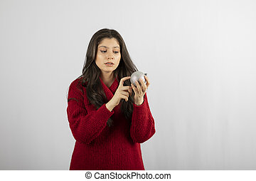 A young woman looking at a Christmas bauble