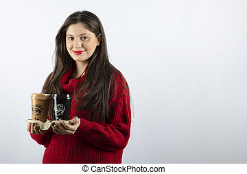 A young woman model in red sweater holding two cups of coffee