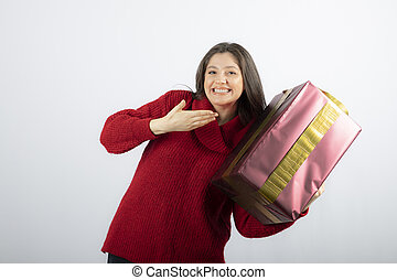 A young woman showing at a Christmas gift box