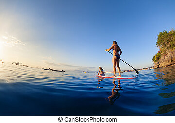 Young mother with little clild paddling on stand up paddleboard