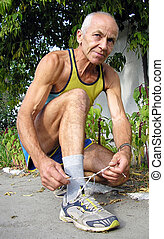 An elderly man in a T-shirt and athletic shorts squatted down and tying shoelaces on sneakers