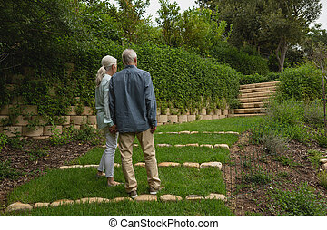 Active senior couple standing together hand in hand at garden