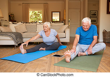 Active senior couple stretching while doing yoga together at home
