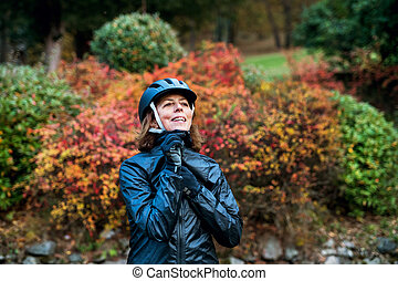 Active senior woman standing outdoors on a road in nature, putting on bicycle helmet.