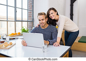 Affectionate happy couple using a laptop