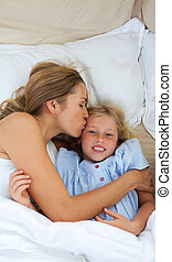 Affectionate mother kissing her daughter