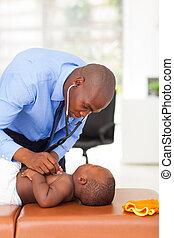 african doctor examining baby boy