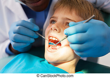 african male dentist examining little boy teeth