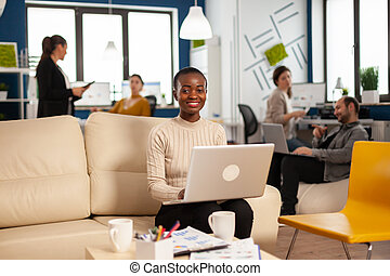 African woman manager sitting on couch in front of camera smiling