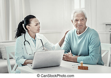Aged grey man sitting and listening to the doctor.