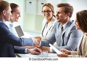 Image of confident businessmen handshaking at meeting