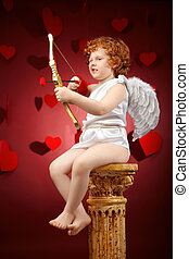 Small aiming boy in an image of the cupid on a red background