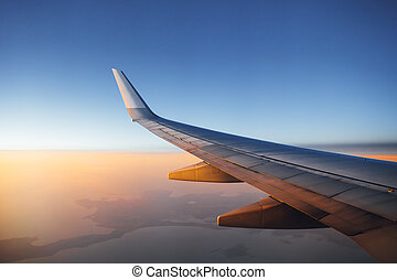 airplane wing against sunset sky background