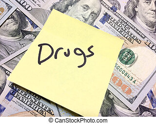 American cash money and yellow paper note with text Drugs