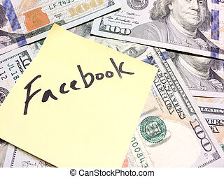 American cash money and yellow paper note with text Facebook