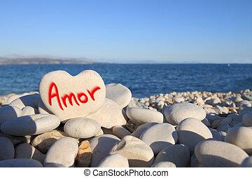 """Amor"" written on heart shaped stone on the beach"