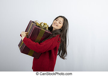 An attractive young woman hugging a Christmas gift over white background