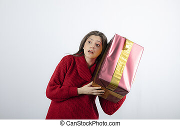 An attractive young woman listening to a Christmas gift over white background