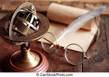 Vintage still life with Armillary sphere globe near quill and scroll
