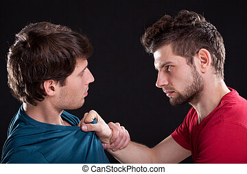 A closeup of an angry man threatening the other by holding his top