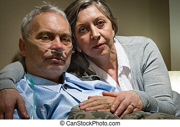 Anxious senior wife holding her sick husband at clinic