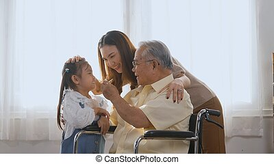 disabled elderly in wheelchair with daughter and granddaughter smiling playing together in living room